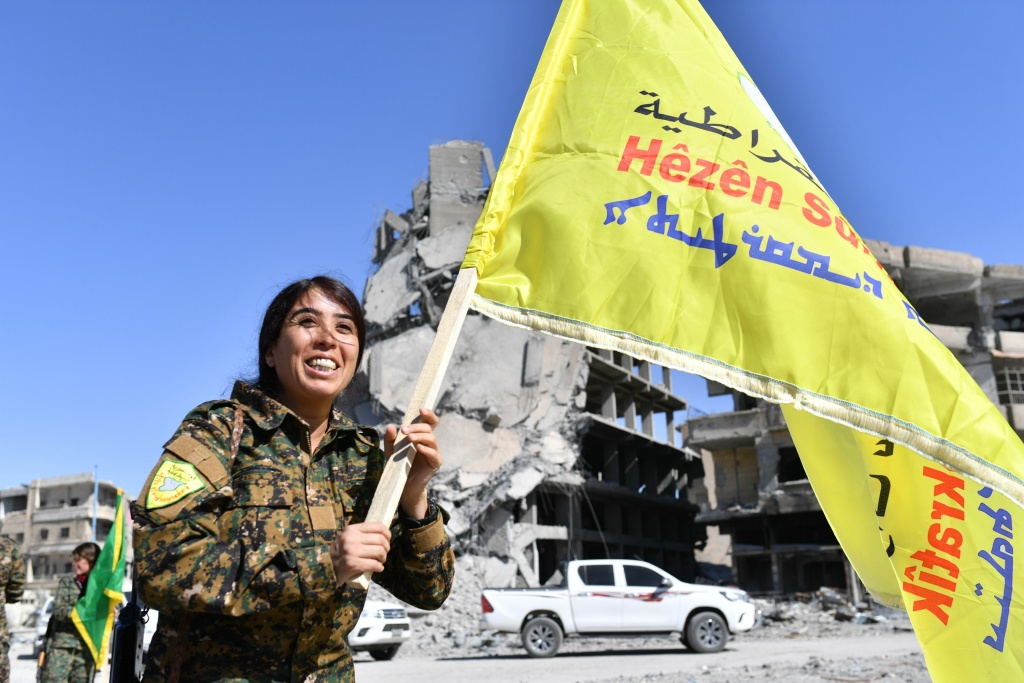 Rojda Felat, a Syrian Democratic Forces (SDF) commander, walks with her group's flag at the iconic Al-Naim square in Raqa on October 17, 2017.