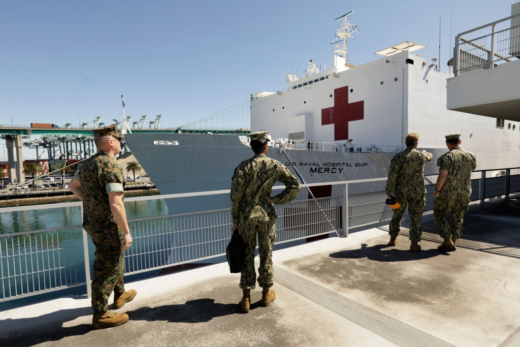 US Navy personnel look at the USNS Mercy hospital ship after it arrived into the Port of Los Angeles on March 27, 2020.