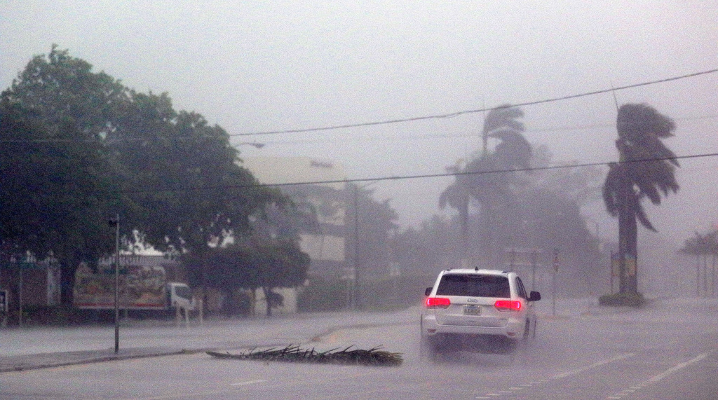 A lone car drives down a road in Boca Raton, Florida as Hurricane Irma strikes on September 10, 2017.