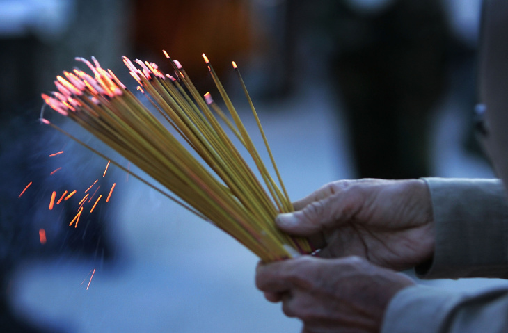 Each year, April brings strong memories and emotions for Vietnamese refugees and their families. Here, a man holds prayer incense on the eve of the 30th anniversary of the Fall of Saigon on April 29, 2005 at the Vietnam War Memorial in Westminster, California.