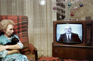 An elderly woman and her cat watch television.