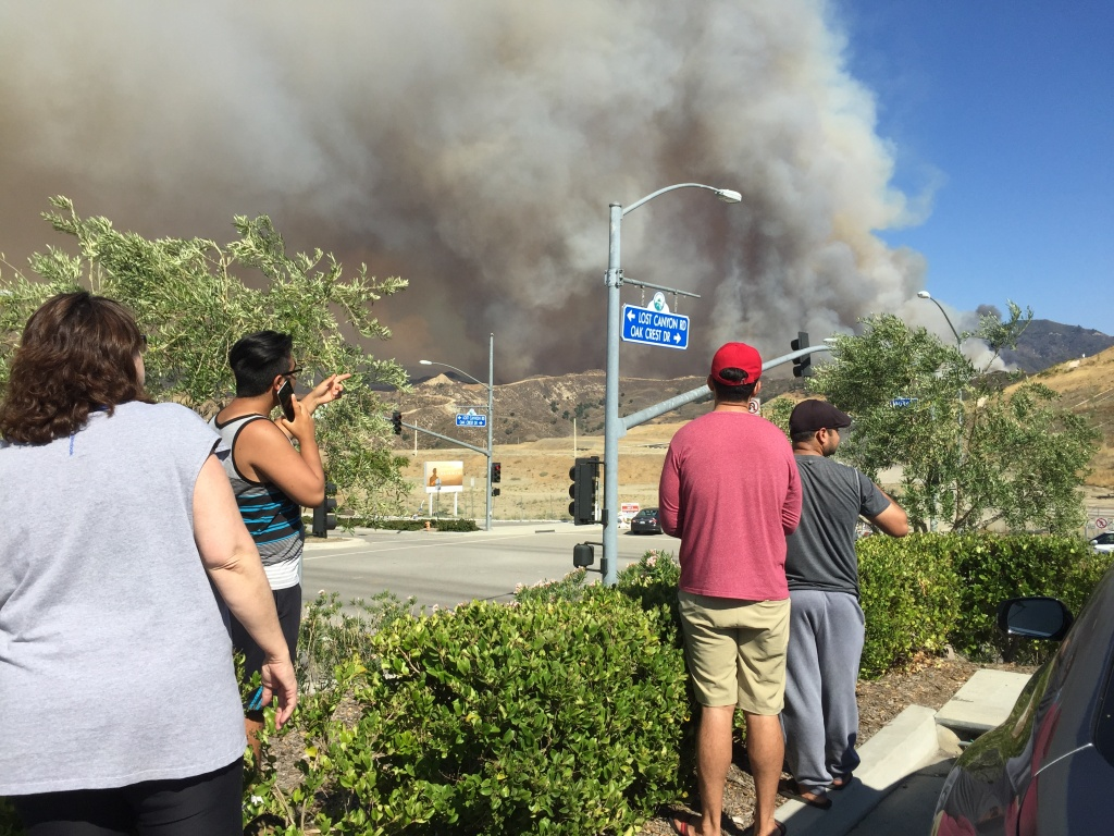 Locals watch the progress of the Sand Fire from a Target parking lot in Santa Clarita on Sunday, July 24, 2016.