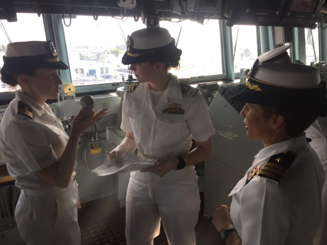 Cdr. Mary Katey Hays (right) listens as the Officer of the Deck and the Junior Officer of the Deck run through the
