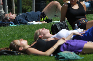 People sunbathe in the warm weather as temperatures climb.
