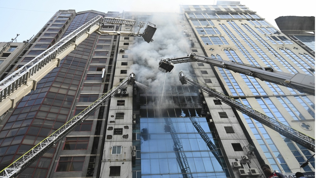 Bangladeshi firefighters work to extinguish a blaze in an office building in Dhaka Thursday. The large and deadly fire — the latest in a string of such disasters in the city — forced people to try to climb down to safety.