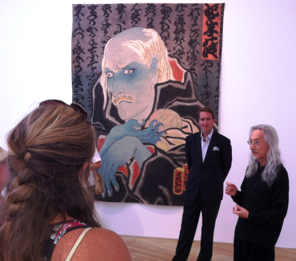 Artist Masami Teraoka explains his AIDS Series painting at Samuel Freeman Gallery as Sam Freeman looks on. 9/11/12.