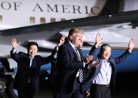President Donald Trump walks with the three Americans just released from North Korea as a goodwill gesture ahead of a planned summit between Trump and Kim Jong Un.