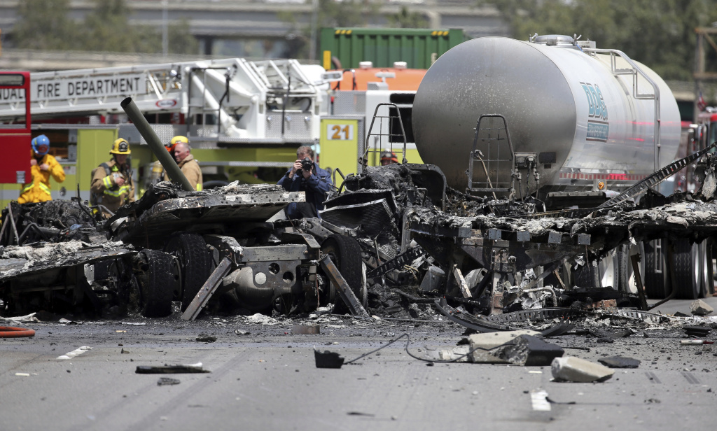 Investigators view the wreckage after a fiery collision of two big trucks and several smaller vehicles killed one person and injured several others while triggering a massive traffic jam on Interstate 5 just north of downtown Los Angeles Tuesday, April 25, 2017.