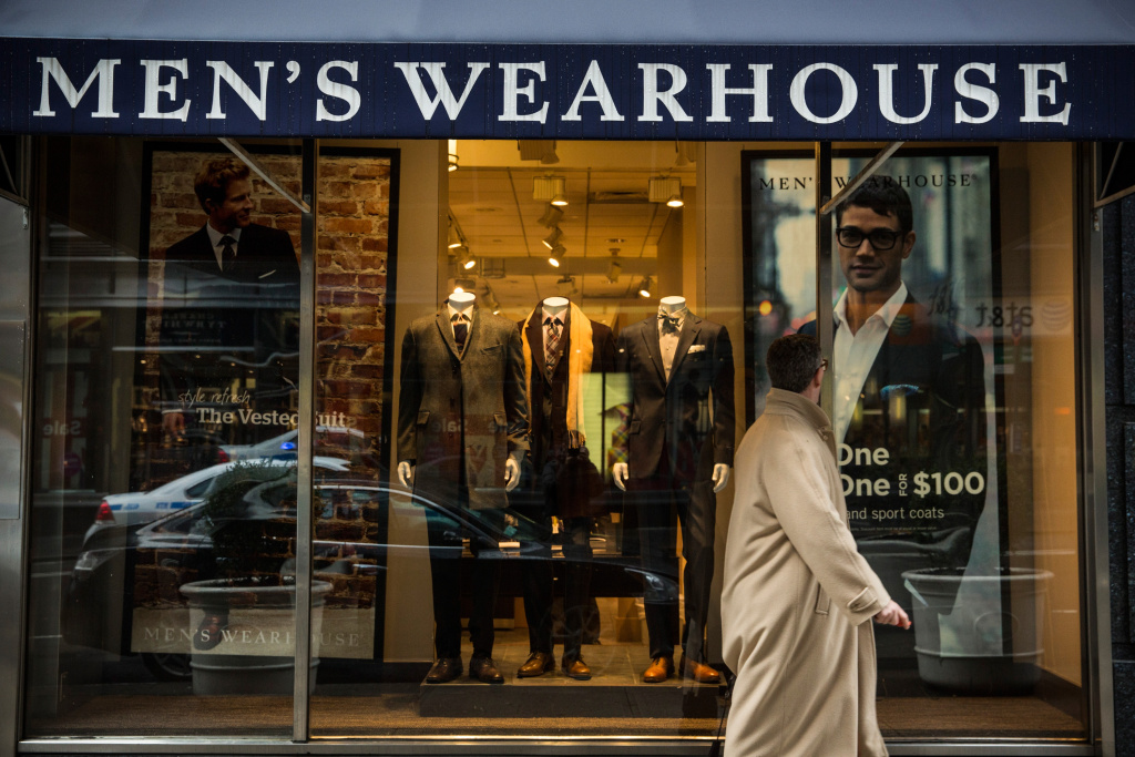 In this file photo, a man walks past a Men's Warehouse store on January 6, 2014 in New York City. Men's Warehouse is buying competitor Jos. A Bank, which also sells men's suits and business wear, for $1.8 billion, it was announced Tuesday.