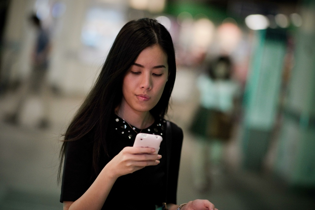 A young woman uses an iPhone in Bangkok, Thailand.