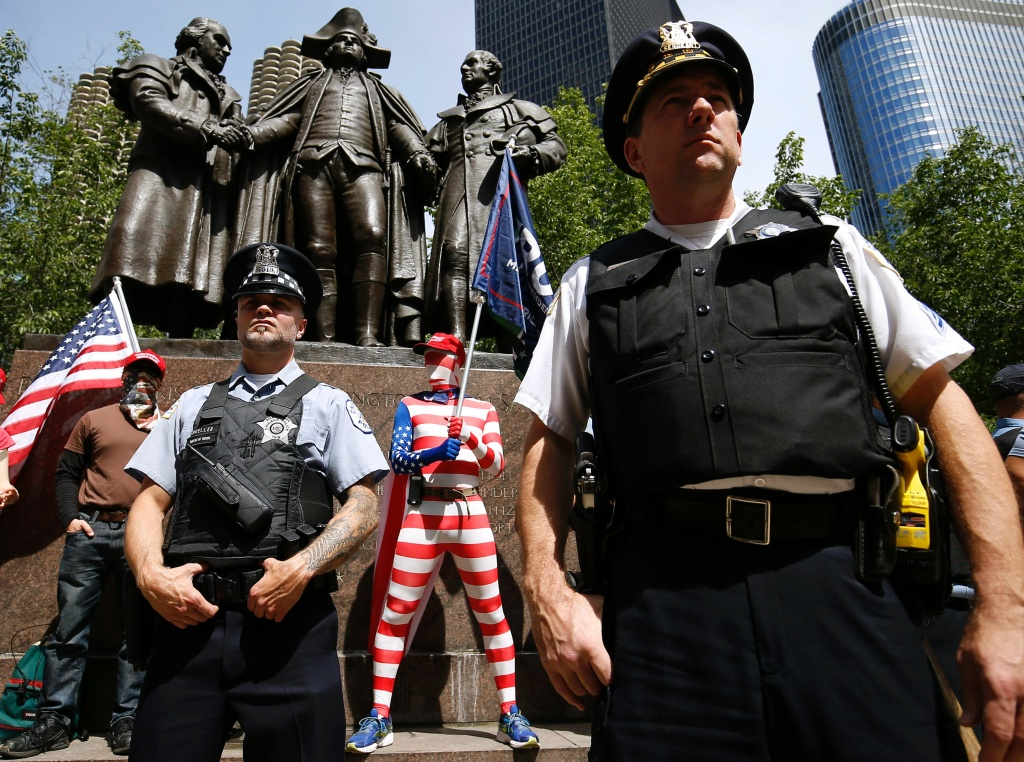 Chicago Police officers form a secure line around   demonstrators with the