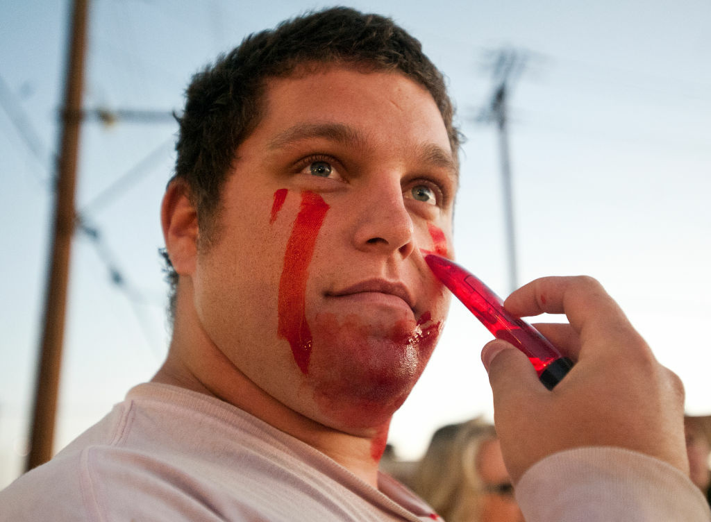 Robert Kibler of Lancaster applies fake blood to his face before the Zombie Walk.
