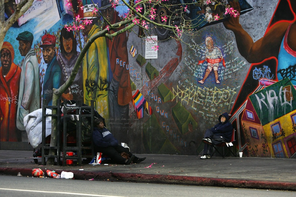 Homeless people sit near a mural after waking up before dawn to dismantle their beds and encampments before businesses open in the downtown L.A.