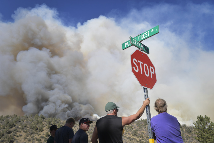 In this file photo, bystanders watch the progress of the Blue Cut Fire near a subdivision of Wrightwood Wednesday afternoon. About 82,000 people were ordered to leave at the peak of the fire threat. Most of those who left are returning now to find their homes intact, though not all.