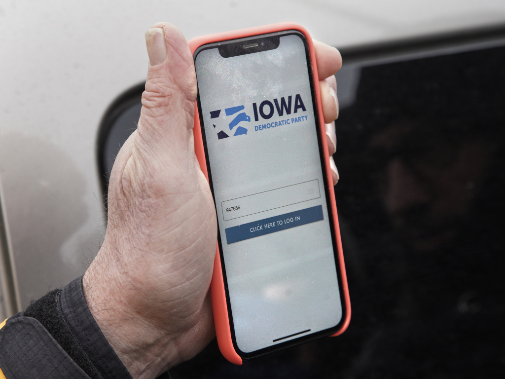 Precinct captain Carl Voss of Des Moines displays the Iowa Democratic Party caucus reporting app on his phone outside of the Iowa Democratic Party headquarters on Tuesday.