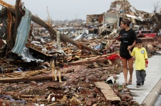 Kimmy Lankford walks with her son Jack, 5, during a walk through their neighborhood after a massive tornado passed through the town.