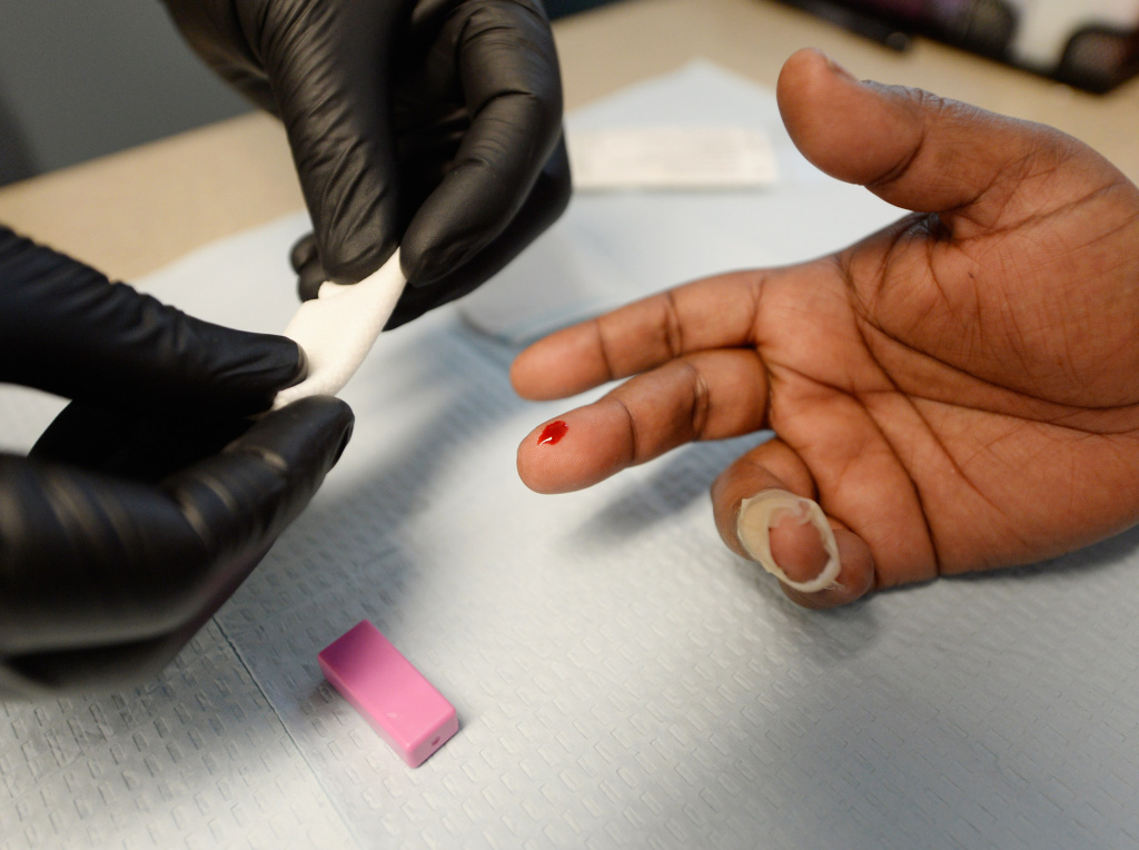 A woman gets an instant  HIV/AIDS test inside a moblile clinic of John Wesley Community Health Institute.