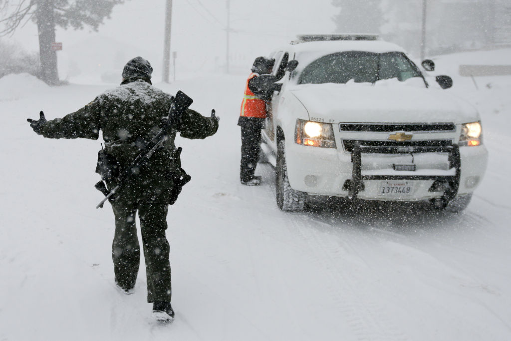 San Bernardino Sheriff's Department officer Steven Spagon mans a check point during the search for fired Los Angeles officer, Christopher Dorner in Big Bear Lake, Calif. Friday, Feb. 8, 2013. Law enforcement officials spent all night searching the snowy mountains of Southern California in searching for Dorner,  who threatened to bring