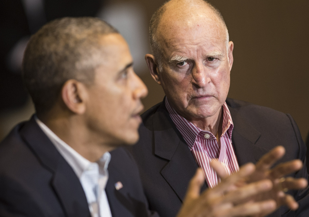California Governor Jerry Brown (R) listens while US President Barack Obama meets with locals at the San Luis Water Facility February 14, 2014 in Firebaugh.