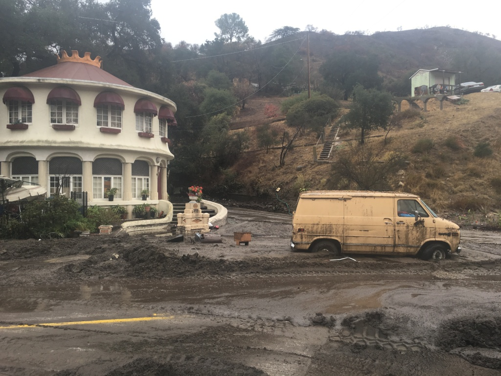 A van on La Tuna Canyon Road is stuck in the mud as its owner waits for a city work crew to dig it out.