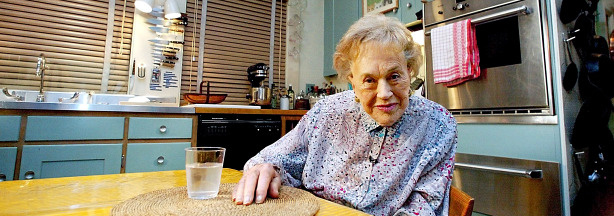 Julia Child sits in her kitchen on August 19, 2002, after it was moved from Cambridge, Massachusetts, and rebuilt as an exhibit marking her 90th birthday at the National Museum of American History in Washington, DC.