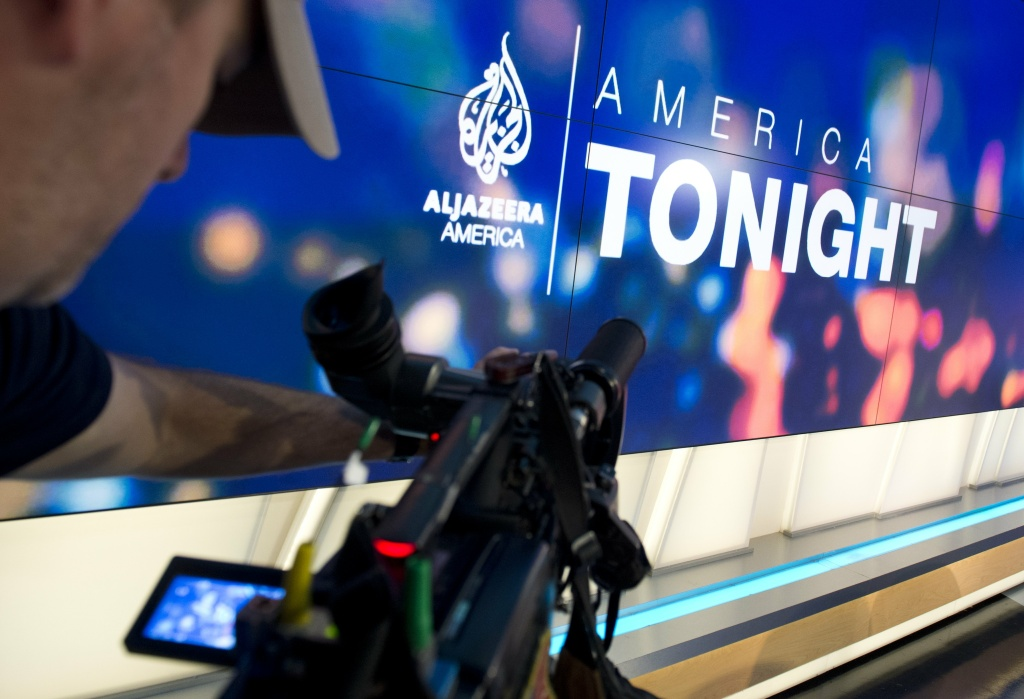 A news photographer films the logo of the new Al Jazeera America nightly news program America Tonight in the network's studio space in Washington, DC. Al Jazeera America, a cable news network set to launch on August 20, will have 12 bureaus in major cities in the US, three broadcast centers, a headquarters in New York City, and around 900 journalists and staff.