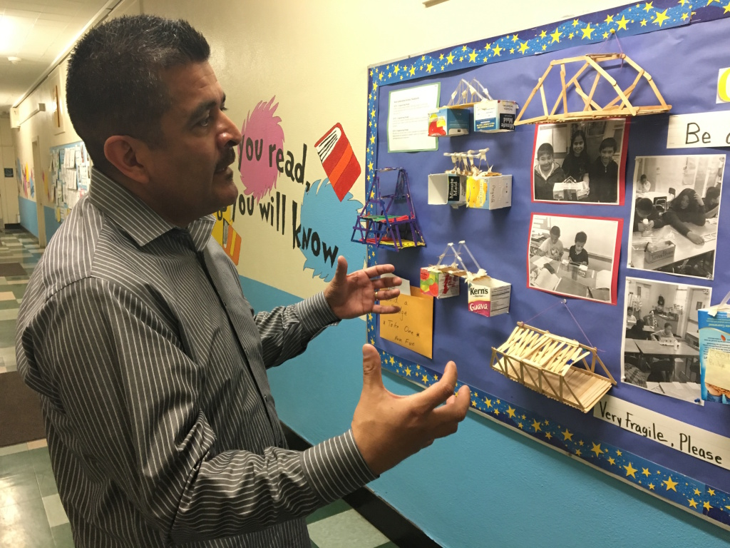 Richard Ramos, principal of Haddon STEAM Academy, shows off students' model bridge-building projects on display in the hallways of the school in Pacoima. He hopes to create a magnet program at Haddon.