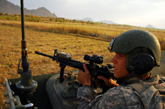 Spc. Riley Sheffield of Boise, Idaho, looks toward a tree line as insurgents fire on the convoy, just after the roadside bomb exploded. Soldiers from Charlie Company exchanged fire with insurgents for over an hour.