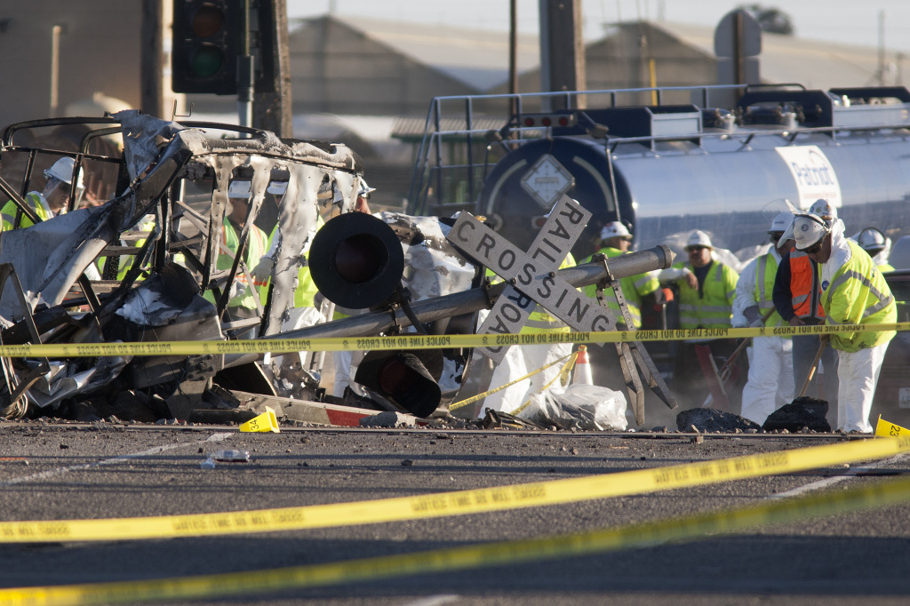 Workers clean up the street near the burned remains of a truck and trailer at the site where a Los Angeles-bound Metrolink train derailed in a fiery collision on the tracks on February 24, 2015 in Oxnard, California.