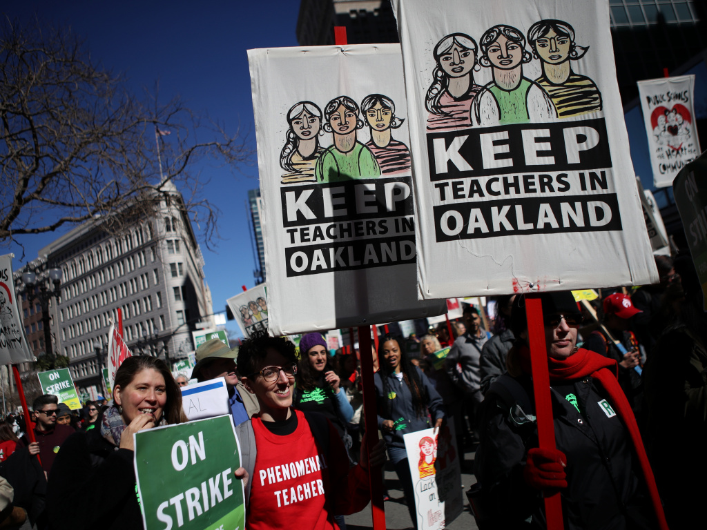 Oakland teachers and parents carry signs as they march to the Oakland Unified School District headquarters this week. Nearly 3,000 teachers in Oakland have gone on strike and are demanding a 12 percent retroactive raise.
