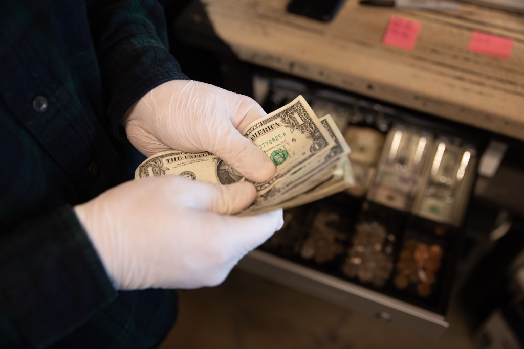 Worker seen counting money with protective gloves before mandatory close at Warehouse 4 Coffee Shop on March 15, 2020 in Vandalia, Ohio.