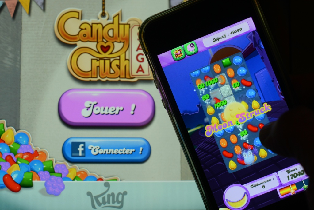 A man plays Candy Crush Saga on his iPhone on Jan. 25, 2014 in Rome. Candy Crush is one of the top online games developed by King.com.