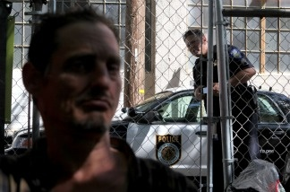 A Sacramento police officer looks in at a homeless man at a 'Safe Ground' encampment August 26, 2009 in Sacramento, California.
