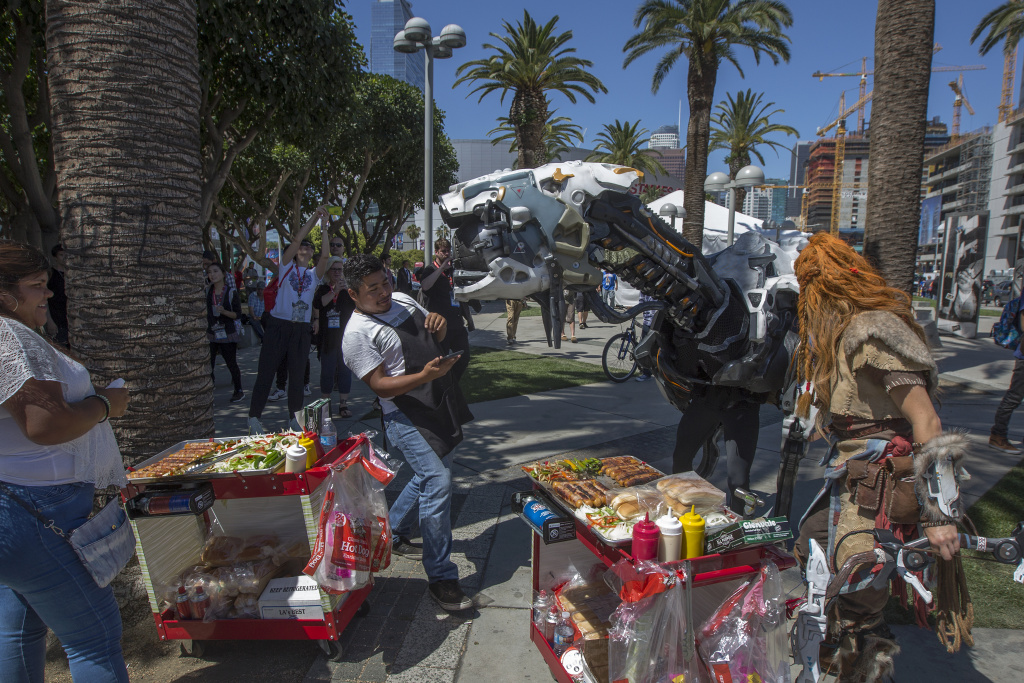 A Horizon Zero Dawn machine character takes interest in a street vendor on opening day of the Electronic Entertainment Expo (E3) at the Los Angeles Convention Center on June 13, 2017 in Los Angeles, California.
