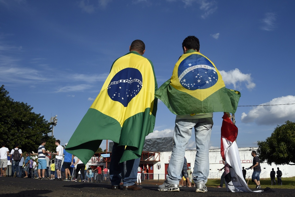 People wearing Brazilian flags arrive at the Santa Cruz Stadium in Ribeirao Prato to attend a France's national football team training session on June 10, 2014, a few days prior to the start of the 2014 FIFA World Cup in Brazil.