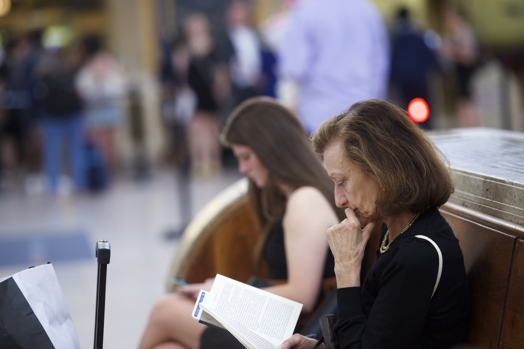 A woman reads a book while in the background travelers prepare to board their Amtrak train.