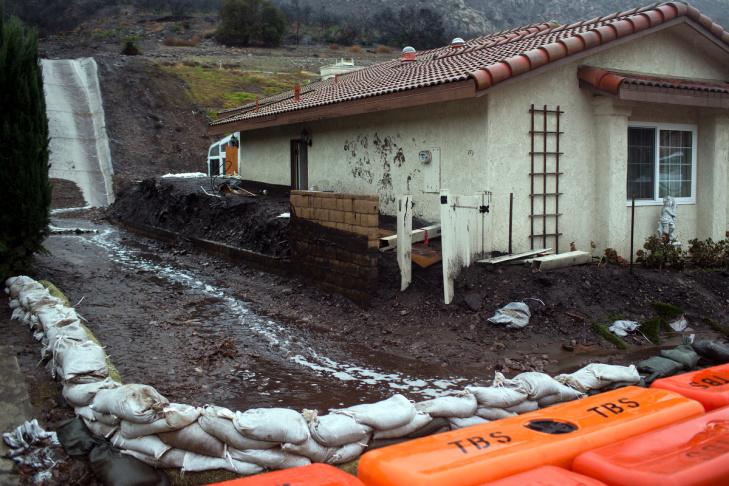 Sandbags lead water and debris flow to the street on San Como Lane in Camarillo Springs on Tuesday afternoon, Dec. 2, 2014. Authorities ordered a mandatory evacuation of the area earlier this morning.