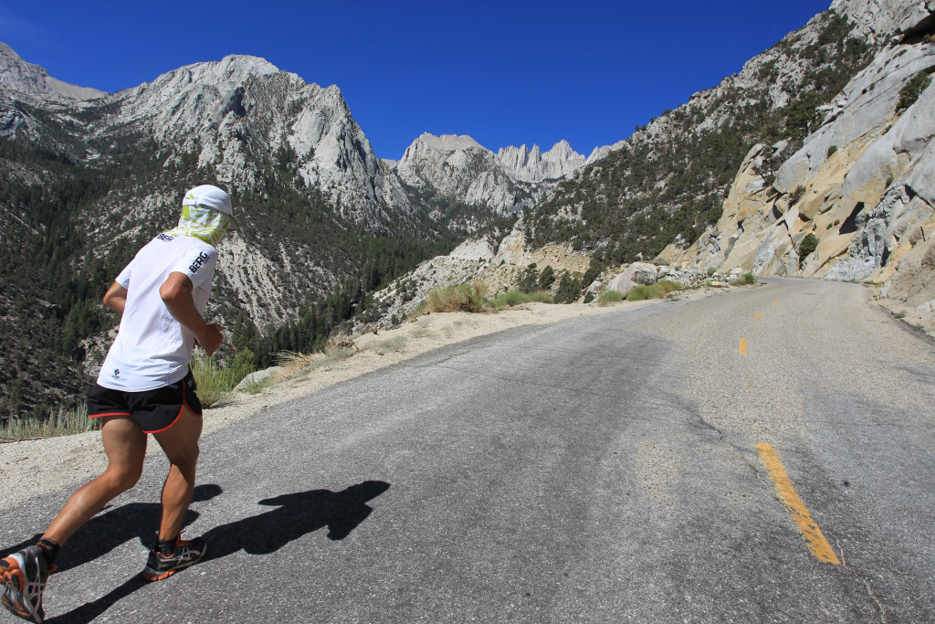DEATH VALLEY NATIONAL PARK, CA - JULY 16:  The tallest U.S. peak outside of Alaska, 14,495-foot Mount Whitney, is seen in the far distance as Carlos Alberto Gomas De Sa from Portugal, a first-time competitor in the event, runs up Whitney Portal Road on his way to win the AdventurCORPS Badwater 135 ultra-marathon race on July 16, 2013 outside of Death Valley National Park, California.