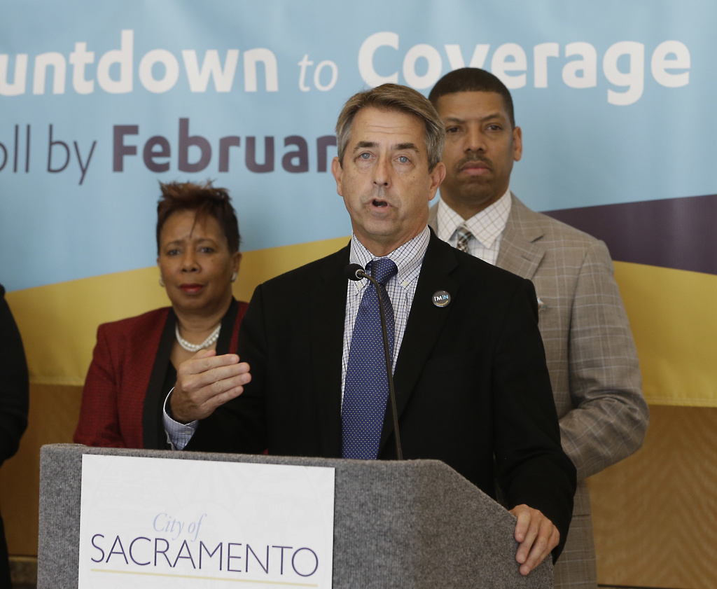 In this Feb. 9, 2015 file photo, Peter Lee, center, executive director of Covered California, the state's health insurance marketplace, discusses health insurance sign ups at a news conference with Sacramento Mayor Kevin Johnson, right, in Sacramento Calif. A 13.2 percent increase in premiums, announced by the Covered California exchange Tuesday, ends the state's two-year respite from double-digit rate hikes.