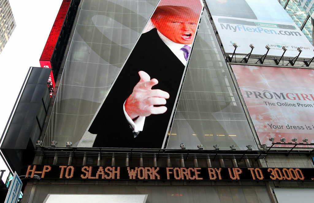 An image of Donald Trump is seen above a message board that is announcing job cuts at Hewlett-Packard in Times Square on May 17, 2012 in New York City. Hewlett-Packard Co. announced plans to cut  25,000 to 30,000 employees as it deals with declining revenue and profits.