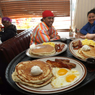Denny's waitress Tahmina Najemyar (R) delivers free Grand Slam breakfasts to customers.
