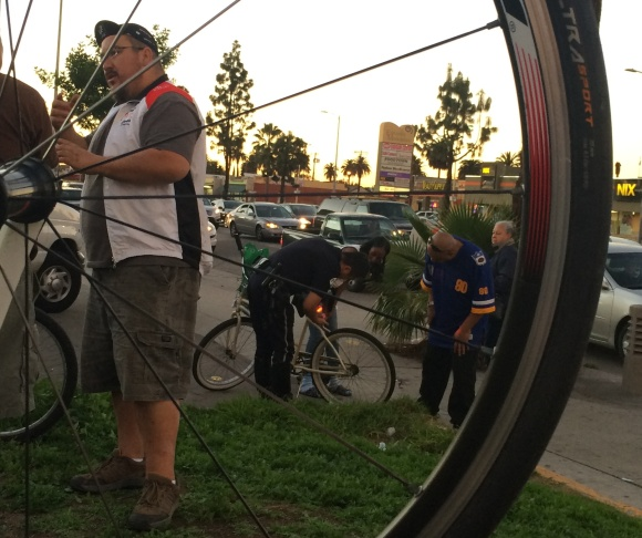 Jose Rojo, volunteer with the LA County Bike Coalition, conducts a survey with a bicyclist before handing out a set of free bike lights. State law requires all cyclists have a front light and a rear reflector when traveling at night.