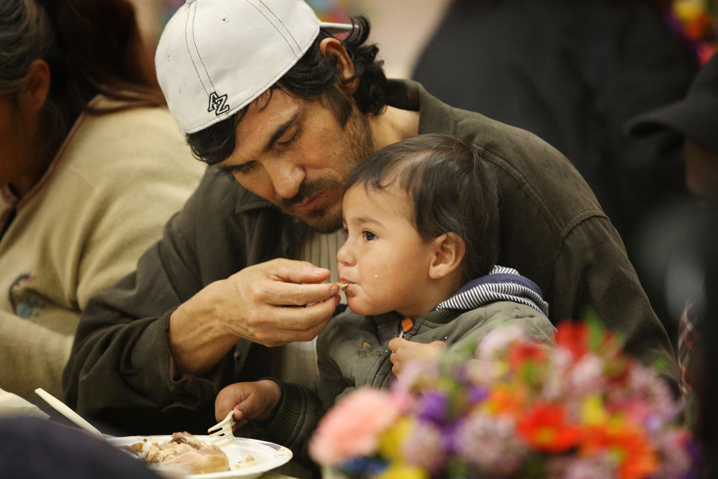 A man and child receive a hot meal during the annual Good Friday Easter event at the Los Angeles Mission in 2009.