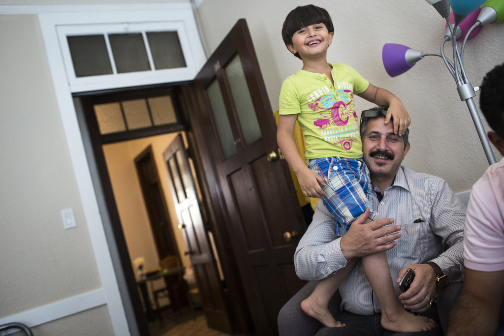 Seven-year-old Abed Rahman Kanjou, left, plays with his father, Abdul Maman Kanjou, in their temporary housing in Pomona on Monday afternoon, Aug. 29, 2016. The refugee family of six arrived in the United States two weeks ago from Syria.