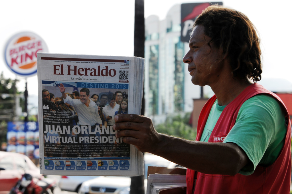 A street vendor sells newspapers in Tegucigalpa, on November 25, 2013, the day after general elections. Both leading presidential candidates in crime-wracked Honduras declared victory late Sunday, setting the stage for a possible round of street protests and violence in one the world's deadliest countries. With more than half the votes counted, conservative Juan Orlando Hernandez was ahead with 34 percent against 29 percent for leftist Xiomara Castro.