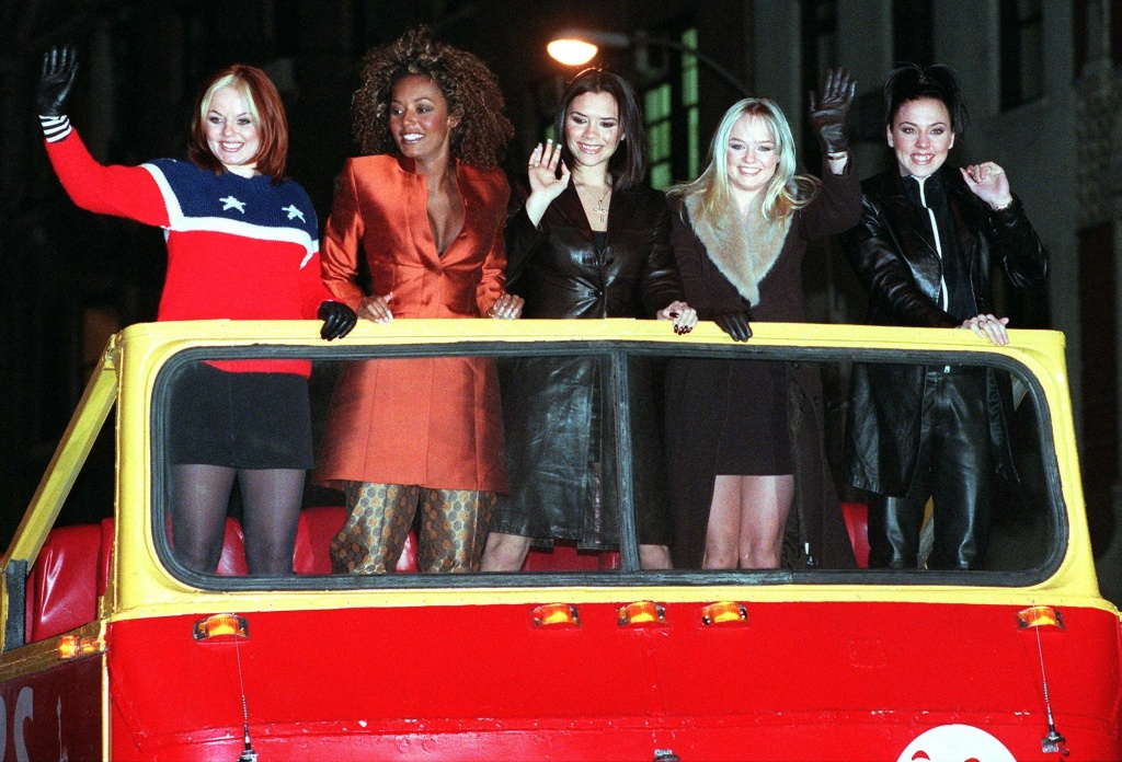 The Spice Girls — Ginger Spice (Geraldine Halliwell), Scary Spice (Melanie Janine Brown), Posh Spice (Victoria Adams), Baby Spice (Emma Lee Bunton) and Sporty Spice (Melanie Jayne Chisolm) —  arrive atop a double decker bus for a screening of their movie