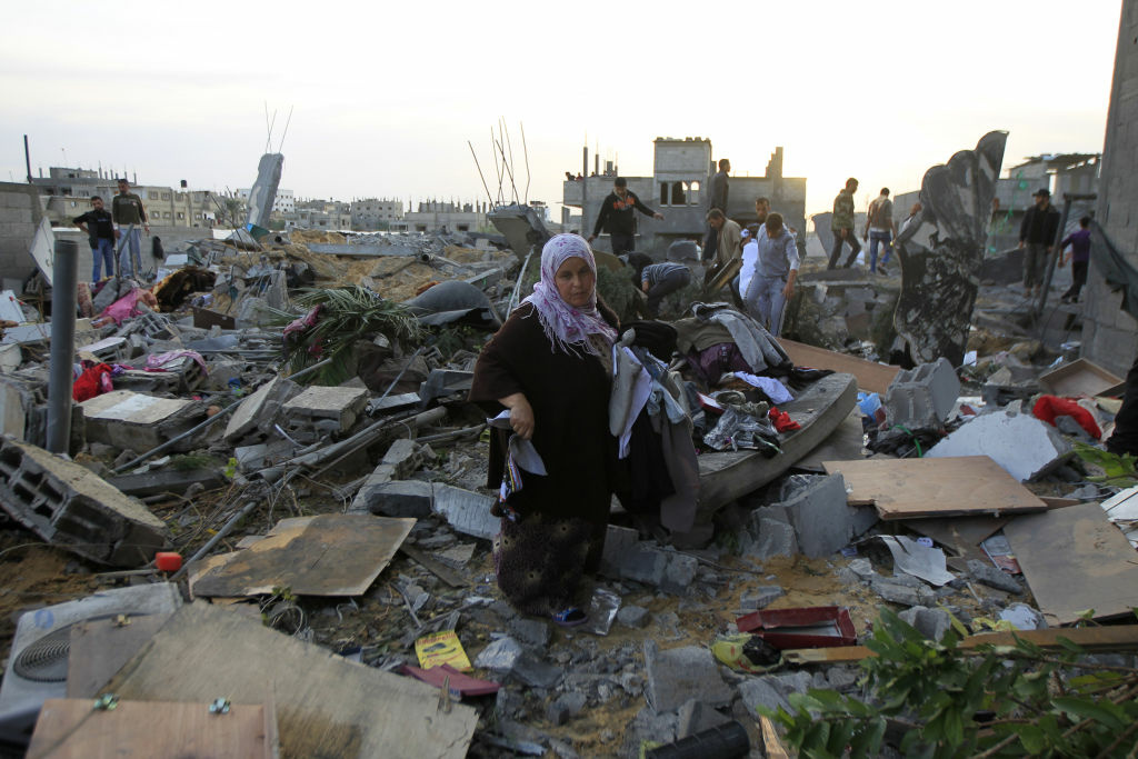 Palestinians gather their belongings as they inspect damages following Israeli air strikes in Rafah in the southern Gaza Strip on November 16, 2012. Israeli officials said the Jewish state was preparing to launch its first ground offensive in four years into the Gaza Strip and the army started calling up reservists.