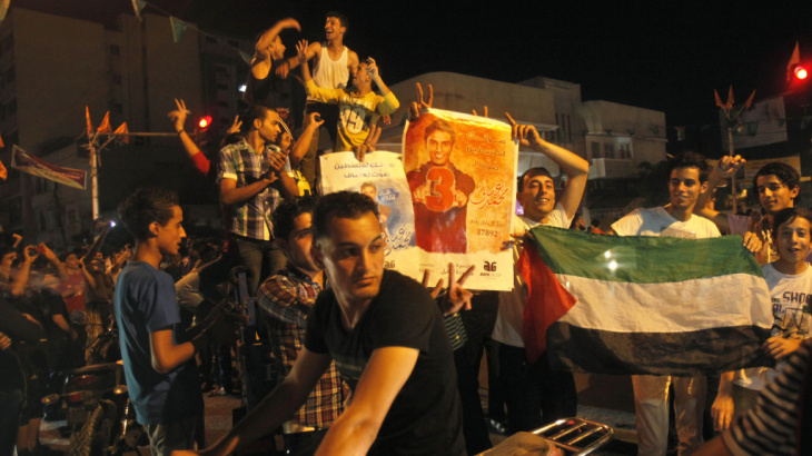 Palestinians dance while holding pictures of singer Mohammed Assaf, as they celebrate his Arab Idol victory along the streets of Gaza City Saturday.