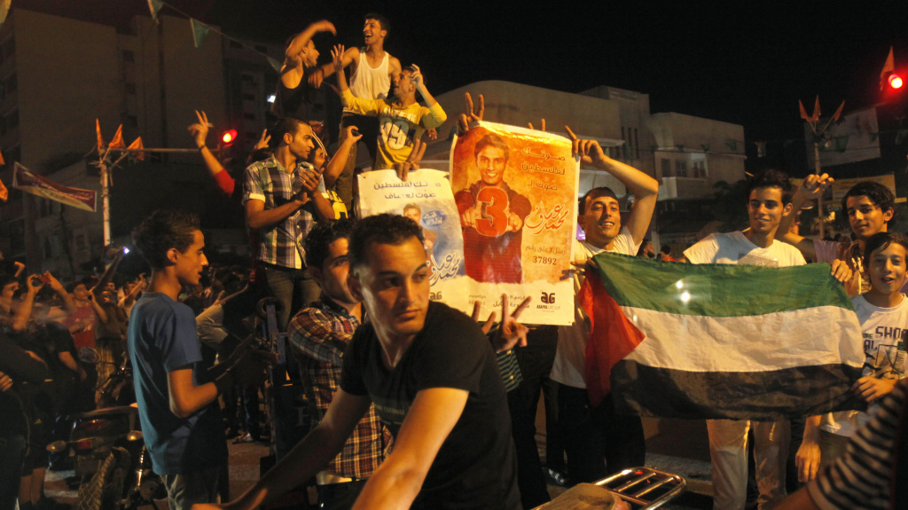 Palestinians dance while holding pictures of singer Mohammed Assaf, as they celebrate his <em>Arab Idol</em> victory along the streets of Gaza City Saturday.