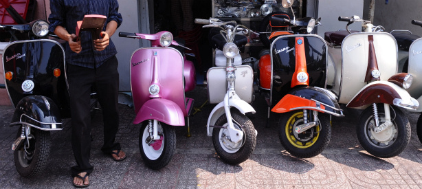 A shop owner stands next to old models of refurbished Vespa scooters.